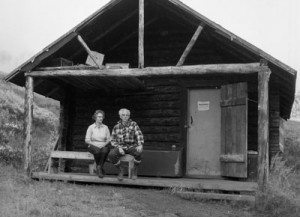 Couple standing in front of cabin: Adolph Murie and Wife